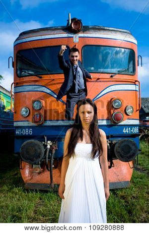 Husband in superman pose on old train and bride in front