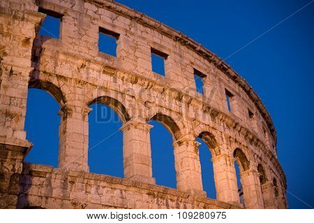 Roman colosseum in evening light and blue sky background