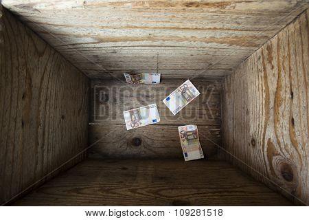 Four 50 euros bills inside a wooden box. Money trap concept