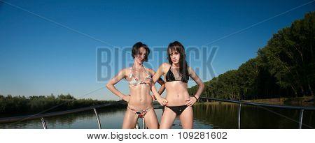 Women enjoying  summer on a boat and posing.