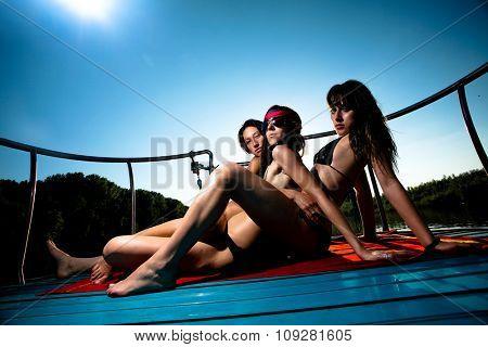 Three women enjoying  summer on a boat and posing under the sun.