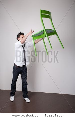 Young trendy man throwing a green chair away