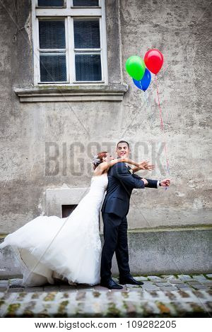 Wedding couple in love having fun. Groom is hiding the balloons from the bride