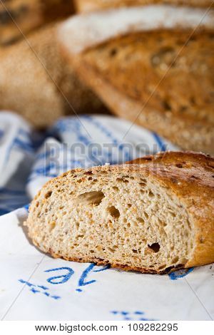 Baked bread sliced, detail. Other breads in background blur