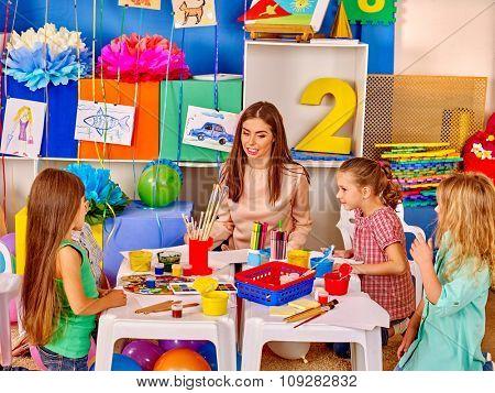 Children with teacher woman painting on paper at table  in  kindergarten preschool.