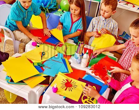 Large Group kids holding colored paper on table in kindergarten .
