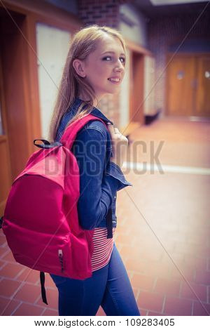 Pretty student with backpack looking at the camera at the university