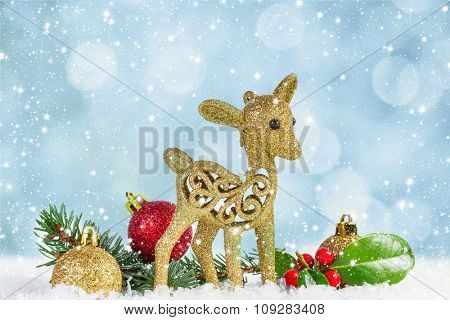 Fawn with fir branch and holly leaves in the snow.