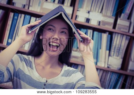 Funny student holding book on her head at the university