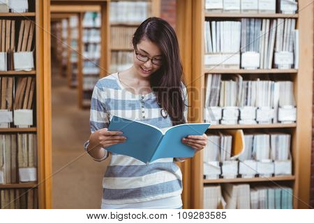 Pretty student reading a book in library at the university