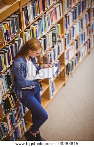 Student reading book in library leaning against bookshelves at the university