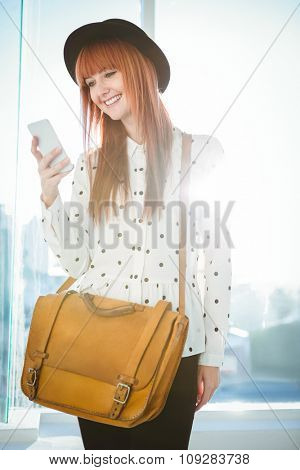 Smiling hipster woman texting with her smartphone in a bright room