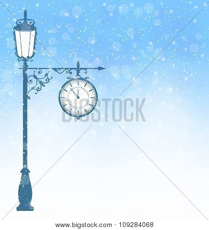 Vintage lamppost with clock in snowfall on blue