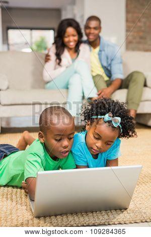 Happy siblings lying on the floor using laptop in the living room