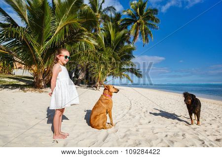 Adorable little girl with pet dogs at beach during summer vacation