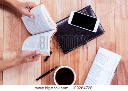 Overhead of feminine hands holding a book with coffee, agenda, newspaper and smartphone on table