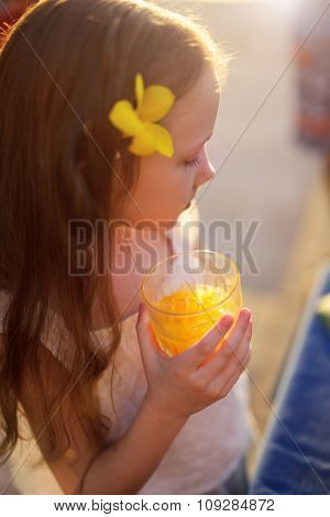 Adorable little girl drinking juice from a glass