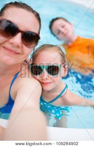 Happy mother and her kids at outdoors swimming pool taking selfie on tropical vacation