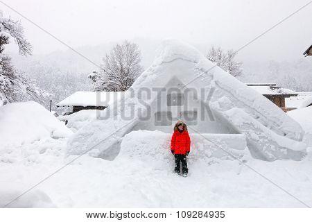 Boy at historic Japanese village Shirakawa-go at winter, travel landmark of Japan