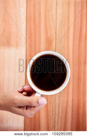 Woman hands holding cup of coffee on wooden desk