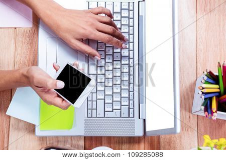 Overhead of feminine hands using laptop and smartphone with stuff on desk