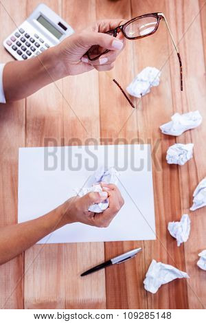 Part of hands making paper ball on wooden desk
