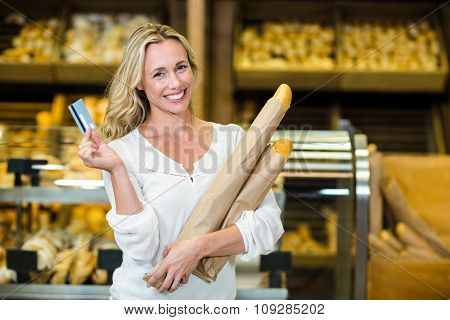 Woman holding bread and credit card in supermarket