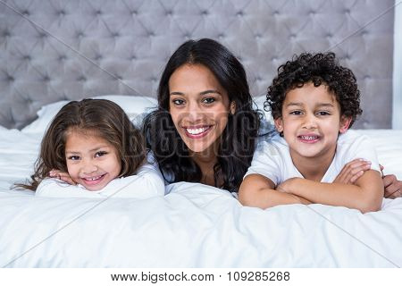 Smiling mother with children on the bed at home