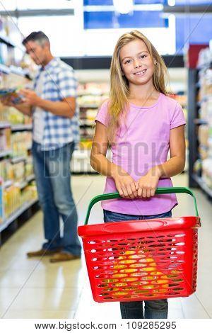 Portrait of smiling child holding basket at the supermarket