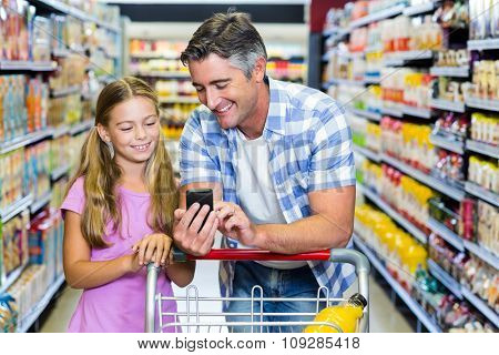 Smiling father and daughter at the supermarket using smartphone