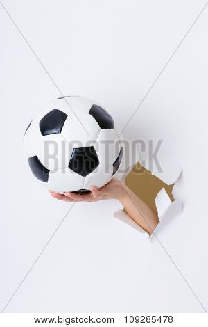 Hand through the hole in paper with soccer ball