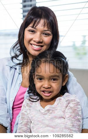 Portrait of happy mother with her daughter in living room