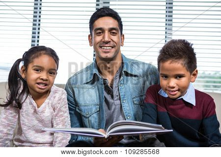 Happy father reading a book for his children in living room