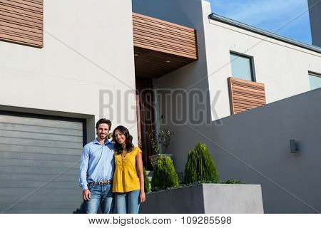 Happy Hispanic couple standing in front of new house