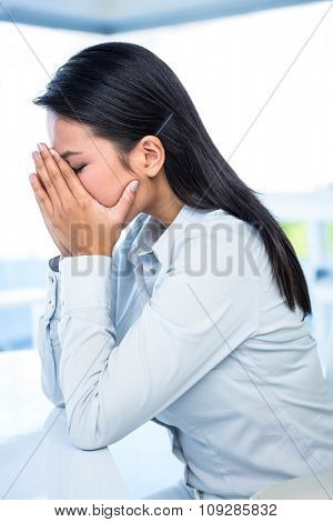 Worried businesswoman covering face at the desk in work