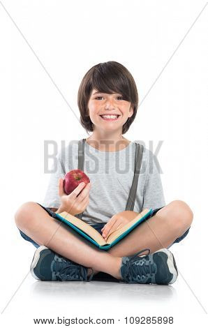 Closeup of smiling little boy studying isolated on white background. Portrait of laughing schoolboy sitting on floor and doing homework. Happy young boy looking at camera with funny face.