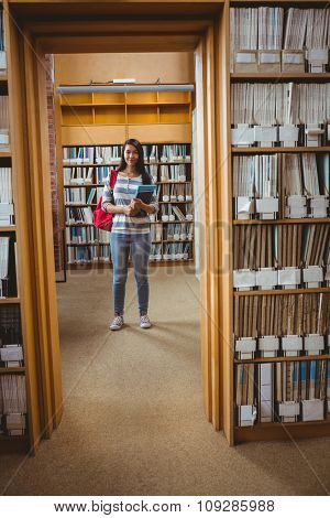 Pretty student standing in library holding a book at the university