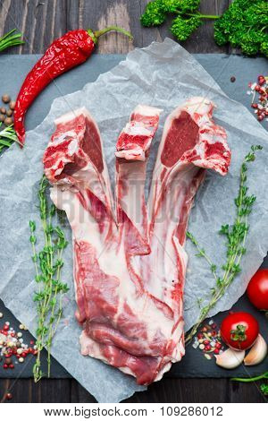 Raw fresh lamb ribs with pepper and thyme on stone board over dark wooden background