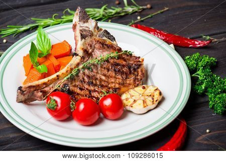 Steak with vegetable garnish on white plate on dark wooden background