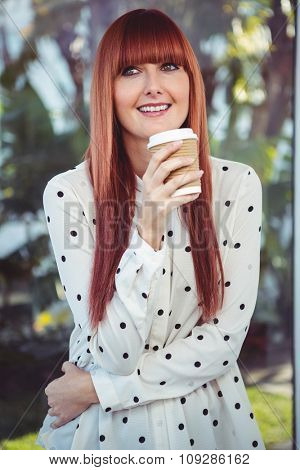 Attractive smiling hipster woman with take-away cup in the garden