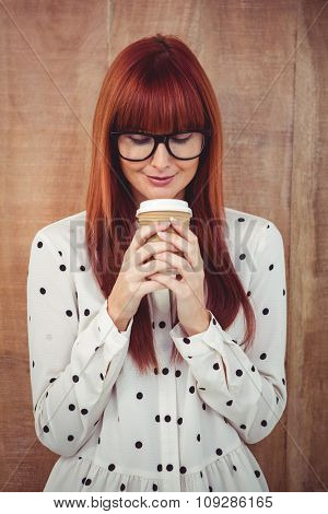 Smiling hipster woman drinking coffee against wooden background