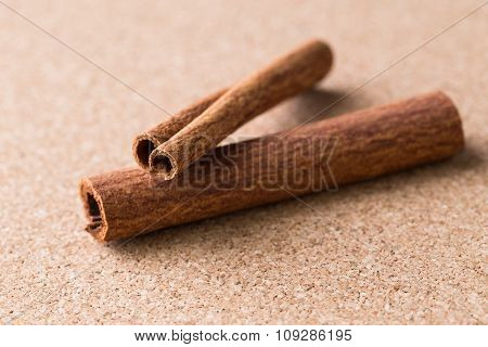 Two Cinnamon Sticks On Corkwood Background.