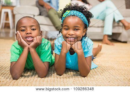 Happy siblings lying on the floor in the living room