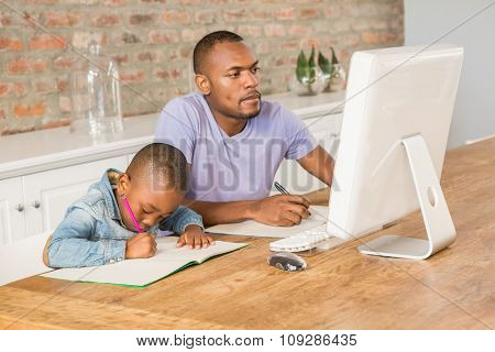 Cute son doing his homework with father in living room