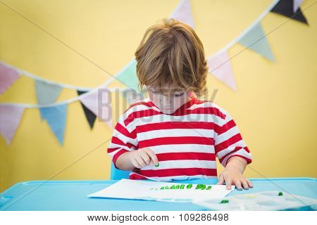 Smiling boy painting a picture at the desk