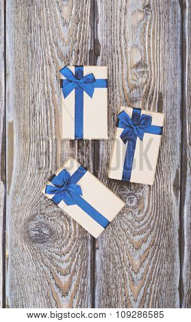 Gift boxes with blue ribbons on dark wooden background