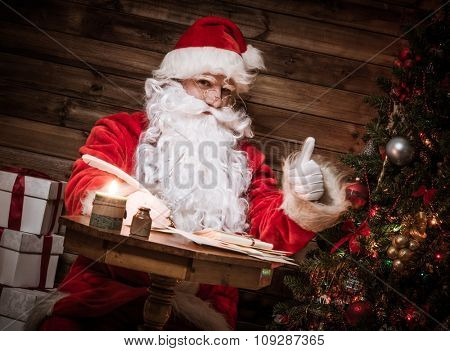 Santa Claus in wooden home interior sitting behind table and writing letters with quill pen