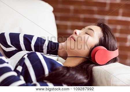 Asian woman lying on the couch listening to music at home in the living room