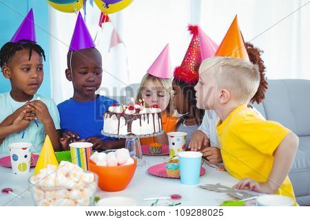 Excited kid enjoying a birthday party blowing out the candles