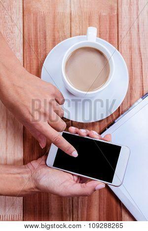 Part of hands using smartphone on wooden desk